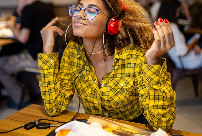 Smiling woman with headphones in cafe