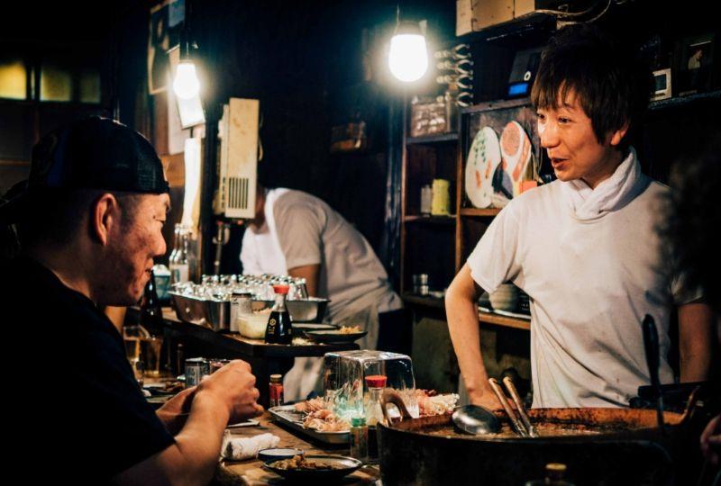 Restaurant owner talking to customer at night
