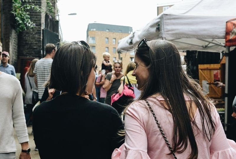 Two women talking on a busy street