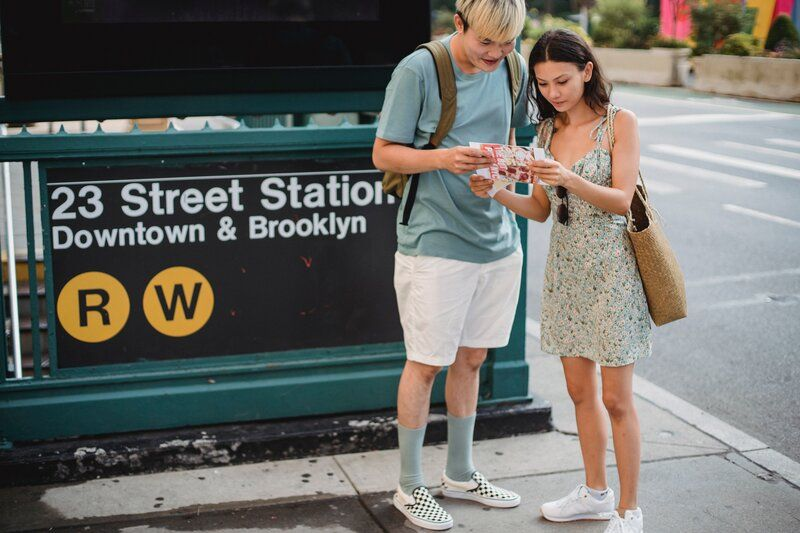 couple looking at a map in front of the subway