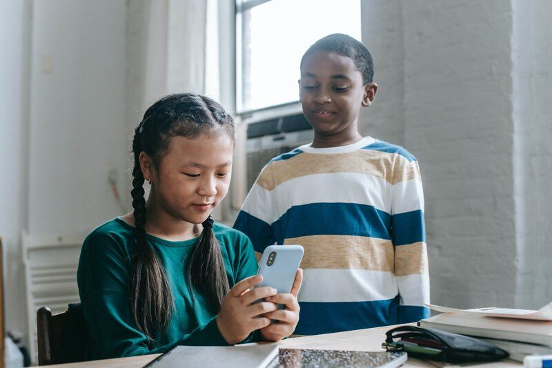 two children texting together